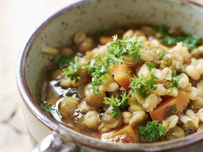 Cup of lentil barley stew with brown lentils, barley, onions, carrots garnished with  parsley